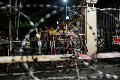 People wait outside the Insein Prison in Yangon as authorities announced more than 5,000 people jailed for protesting against a February coup would be released