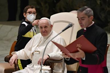 A boy makes clear he wants Pope Francis's cap during surprise appearance at Vatican audience