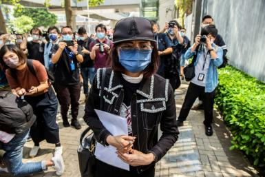 The mother of Poon Hiu-wing (C), a 19-year-old woman who was murdered by her boyfriend during a visit to Taiwan in 2018, leaves after speaking to the media in Hong Kong