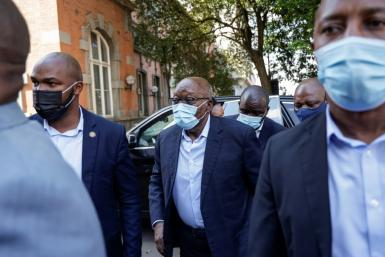Zuma stepped briskly out of his vehicle and up to the building's entrance surrounded by security personnel