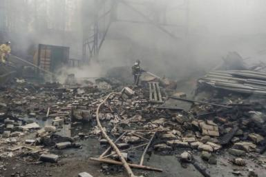 Firefighters working their way through the debris at the damaged factory building in the region of Ryazan