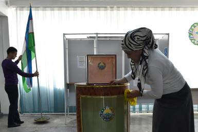 Local election commission members prepare a polling station for Sunday's presidential election in Tashkent