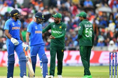 Rivals: Pakistan's Mohammad Amir and Babar Azam speak with India captain Virat Kohli and Vijay Shankar at the 2019 World Cup in Manchester