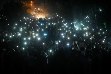 TLP supporters use mobile phone flashlights during their protest march towards Islamabad on Friday
