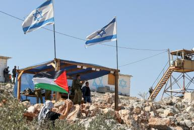 A Palestinian man waves his flag next to the Israeli outpost of Evitar in the occupied West Bank on October 10