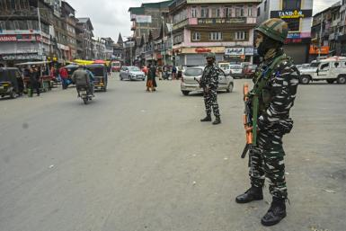 Indian paramilitary troopers stand guard at a market in Srinagar on October 24, 2021