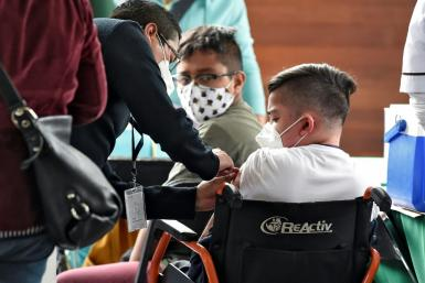 A minor in Mexico City is inoculated with the Pfizer-BioNtech vaccine against Covid-19 as part of the capital city's plan to vaccinate at-risk youths