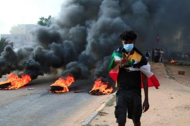A Sudanese protester draped in the national flag flashes a V-for-victory sign next to burning tyres at a demonstration in Khartoum