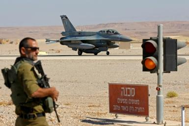 """An Israeli soldier stands guard as an F-16 fighter lands during the """"Blue Flag"""" multinational air defence exercise"""