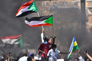 In this file picture taken on October 21, 2021, Sudanese demonstrators raise national flags as they take part in a protest in the city of Khartoum Bahri to demand the government's transition to civilian rule