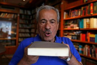 Muhammad Salem al-Nouri blows dust off a book at the Dar al-Maarifa library, which was forced to close in 2000 because of poor sales and growing costs