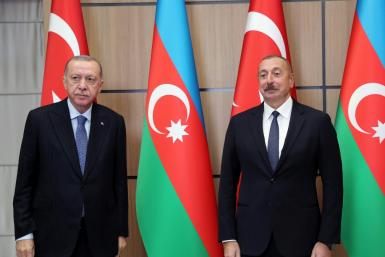 This handout photograph taken and released on October 26, 2021, by the Turkish Presidential Press Service shows Turkey's President Recep Tayyip Erdogan (R) as he is welcomed by Azerbaijan's President Ilham Aliyev (L) in Zangilan