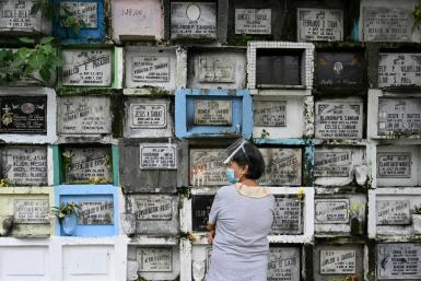 A woman prays in front of the grave of a relative at a cemetery in Manila ahead of All Saints' Day