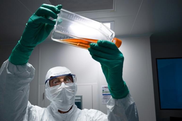 A lab technician in Personal Protective Equipment (PPE) looks at a reagent bottle before performing vaccine tests at French pharmaceutical giant Sanofi's lab in Val de Reuil
