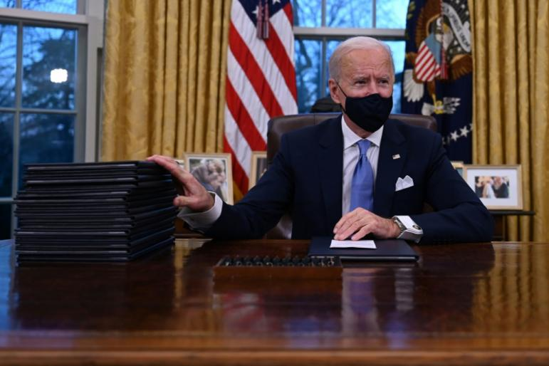 US President Joe Biden prepares to sign a series of orders in the Oval Office of the White House on his first day in office