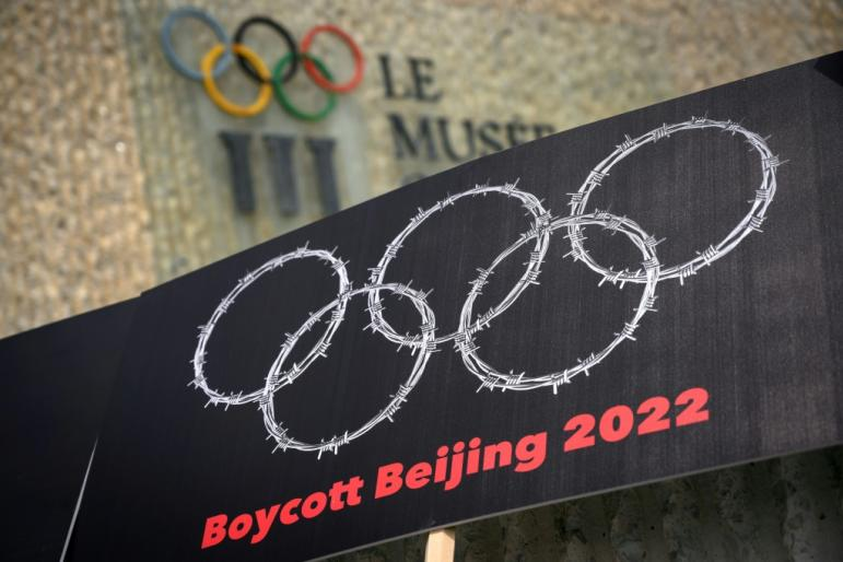 Tibetan and Uyghur activists hold up a placard showing the Olympic rings as barbed wire during a June 2021 protest outside the Olympic Museum in Lausanne, Switzerland