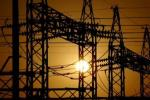 The sun sets behind electric pylons in Allahabad Feb. 22, 2006.