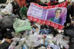 A protester displays a banner of the ousted President Ben Ali found in the garbage, as he helps municipality workers clear up rubbish in Tunis