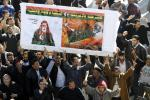 Protesters opposed to leader Muammar Gaddafi hold a poster of Omar Mokhtar in the centre of the city of Zawiyah
