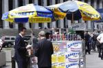 British PM David Cameron buys a hot dog with New York City Mayor Michael Bloomberg outside Penn Station in New York