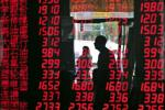 An investor is reflected in a screen showing stock information at a brokerage house in Shenyang