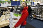 A customer holds an armload of electronics as he waits to check out at a Best Buy store in Pineville, North Carolina
