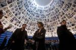 Hollywood actors Austin Nichols (L), Mary Lynn Rajskub (C) and Shaun Sipos (R) stand under pictures of Jews killed in the Holocaust as they listen to a guide during a visit to the Hall of Names at Yad Vashem's Holocaust History Museum in Jerusalem