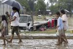 Residents walk past trucks swept away by flash floods due to heavy rains brought by Typhoon Washi, known locally as Sendong, in Iligan city, southern Philippines December 17, 2011.