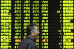 An investor yaws as he walks past an electrical board showing stock information at a brokerage house in Nanjing