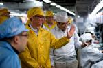 Handout photo shows Apple CEO Cook talking to employees as he visits the iPhone production line at the new Foxconn Zhengzhou Technology Park in Henan