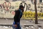 A young man wearing a mask to protect him from tear gas passes a wall with graffiti of Chairman of the ruling Supreme Council of the Armed Forces (SCAF) Mohamed Hussein Tantawi, in the shadow of clashes between police and protesters near the Interior Mini