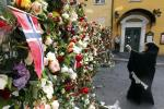 A Muslim woman takes pictures near a sea of floral tributes placed outside the Oslo Cathedral