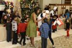 First Lady Michelle Obama (C) chats with children of military families as they gather to enjoy holiday decorations and treats