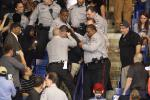 A protester is escorted by police from a Donald Trump rally.