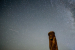 Shooting stars cross the night sky over a wooden idol near the village of Ptich some 25km away from Minsk, during the peak of the annual Perseid meteor shower on August 15, 2015.