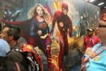 Convention-goers walk by a poseter of Supergirl and The Flash during Comic-Con International in San Diego, California on July 21, 2016