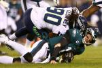 Philadelphia Eagles quarterback Carson Wentz, bottom, is hit by Seattle's Jadeveon Clowney and sent off for the rest of Sunday's NFL playoff game