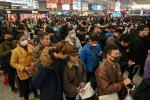 At Shanghai's Hongqiao Railway Station some travellers wear face masks as they wait to board their trains