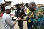 A policeman in Lagos distributes flyers about measures to prevent coronavirus