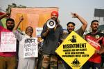 Farmers hold placards and shout slogans during a protest at the Delhi-Haryana state border