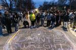 """People write """"Justice for Daunte Wright"""" on the road in a suburb of Minneapolis, Minnesota"""