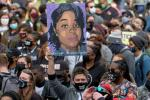 A protestor displays a portrait of Breonna Taylor during a rally in remembrance on the one year anniversary of her death in Louisville, Kentucky, on March 13, 2021