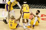 Anthony Davis #3 and Kyle Kuzma #0 of the Los Angeles Lakers reacts as they are helped up off the floor by Kentavious Caldwell-Pope #1 and Andre Drummond #2, after their collision, during the first quarter against the LA Clippers at Staples Center