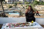 A Palestinian Muslim woman prays at the grave of a relative in Beit Lahia in the Gaza Strip on the first day of Eid al-Fitr, as the worst flare-up of Israeli-Palestinian violence in seven years clouds the three-day holiday