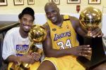 Kobe Bryant (L) of the Los Angeles Lakers holds the Larry O'Brian trophy as teammate Shaquille O'Neal (L) hold the MVP trophy after winning the NBA Championship against Indiana Pacers 19 June, 2000