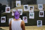 A man looks at pictures of missing residents of the partially collapsed building at a makeshift memorial in Surfside, north of Miami Beach, on June 25, 2021