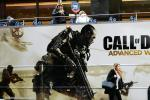 """A woman walks past a bus advertising video game """"Call of Duty"""" made by Activision Blizzard, which is being accused of workplace harassment of female employees"""