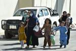Afghan woman with children, hoping to leave Afghanistan, walk through the main entrance gate of Kabul airport on August 28, 2021 as the US military prepared to leave