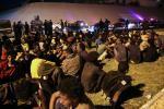 Migrants sit on the ground after being recaptured by Libyan security forces following an escape attempt