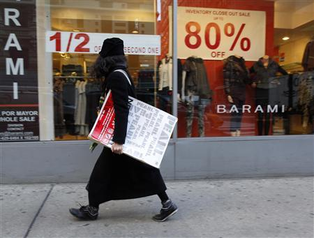 A woman walks past a retail store in the fashion district of New York